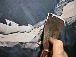 smoothing-the-caulk-with-a-wet-putty-knife-for-plaster-ceiling-repair